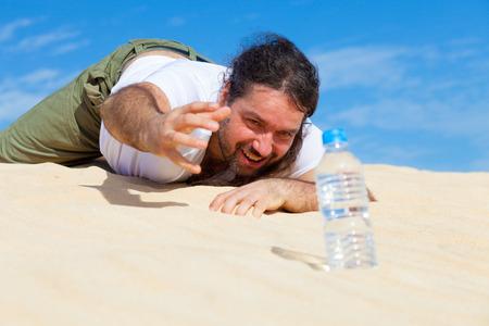 sediento: hombre sediento alcanza para una botella de agua en el vacío