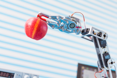robot arm: red apple in a  robot  arm