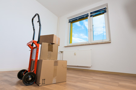 cardboard boxes in an empty apartment. moving to a new apartment Hand Truck Stock Photo