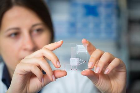 laboratorio: Un laboratorio en el chip es un dispositivo integra varios procesos de laboratorio en un solo dispositivo, en mano de la mujer Foto de archivo