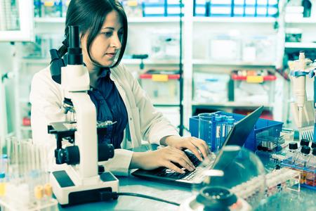 実験助手をコンピューターの DNA シーケンスの分析します。 写真素材