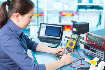 ic: Woman with a tester and a printed circuit board Stock Photo