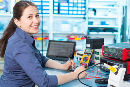 repair computer: Woman with a tester and a printed circuit board Stock Photo
