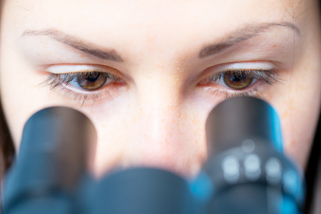 Vrouw van de arts die in microscoop Stockfoto