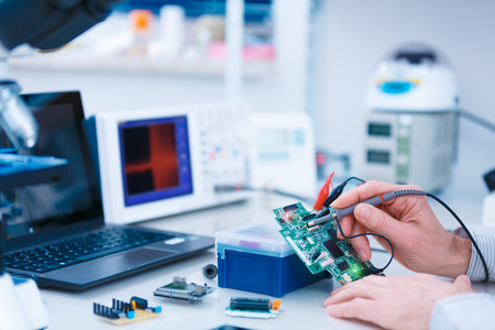 Using the microscope electronics laboratory Stock Photo