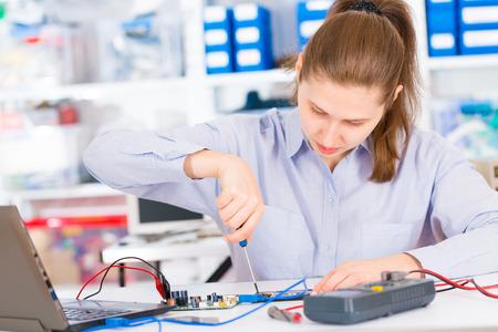 trabajando en computadora: Mujer con un probador y una placa de circuito impreso