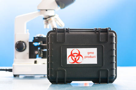 hazard symbol: Safe case with GMO product and microscope in laboratory