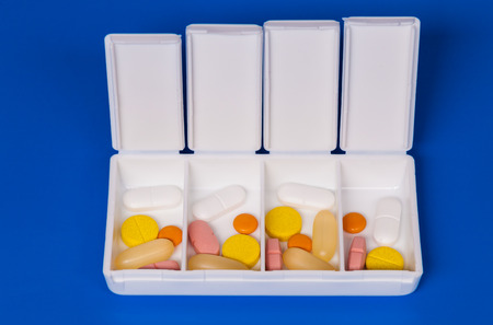 pillbox: Dispenser with medicine pills on a blue background