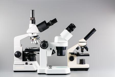 monocular: Monocular, binocular and trinocular microscopes on grey background