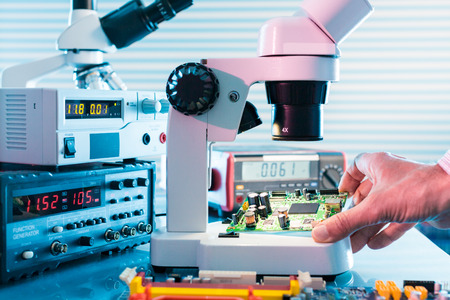 control de calidad: Laboratorio de microelectrónica con los instrumentos de medición y microscopios. Tarjeta de circuitos electrónicos en la mano Foto de archivo