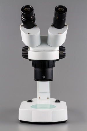 science education: Incident binocular research microscope on gray background