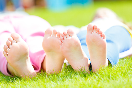 dirty feet: Children  heels on the grass Stock Photo