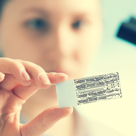 microchip: In the laboratory technician looks at slides through a microchip Stock Photo
