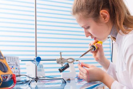 woman engineer: Girl solder wires