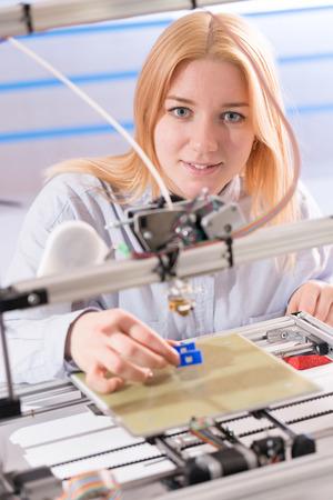 A student girl print prototype on 3D printer
