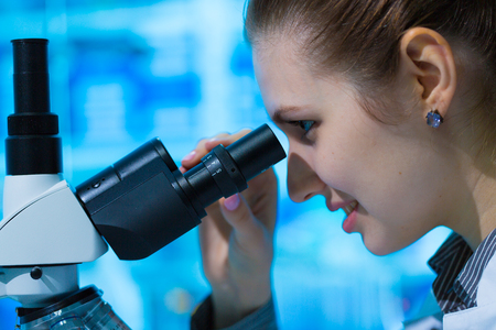 research science: Female scientist looking through a microscope in laboratory