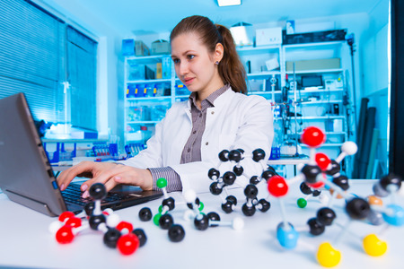 molecule: young woman scientist working at the laboratory. Model of molecule on a table