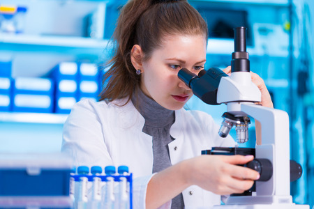 laboratorio: Científico de sexo femenino que mira a través de un microscopio en el laboratorio Foto de archivo