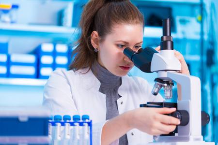 équipement: Femme scientifique regardant à travers un microscope dans le laboratoire