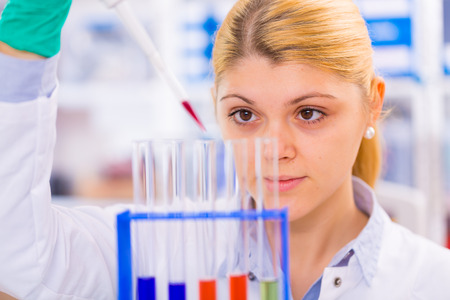pcr: Young female scientist loads samples for DNA amplification by PCR into plastic tubes