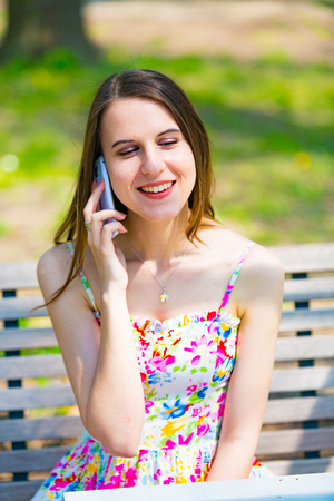 blonde haired: Happy beautiful blonde girl calling by phone in a summer park
