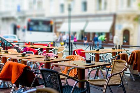 Treet vista di una terrazza Cafe con tavoli e sedie in città europea Archivio Fotografico - 45365404
