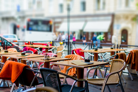 treet view of a Cafe terrace with tables and chairs in european city Foto de archivo