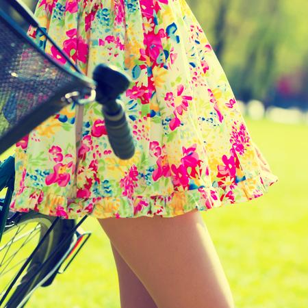 mujeres fashion: chica en vestido corto con la bicicleta en el parque de verano