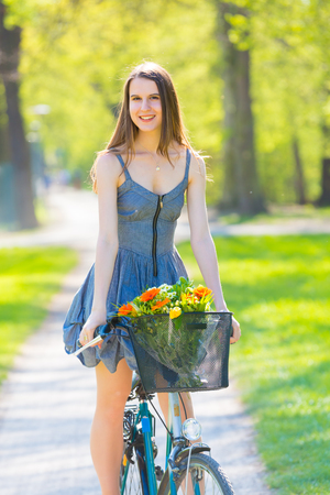 summer dress: Young woman in short grey dress with long hair rides a bicycle with basket and flowers tour summer city park, look and smile on flowers bouquet