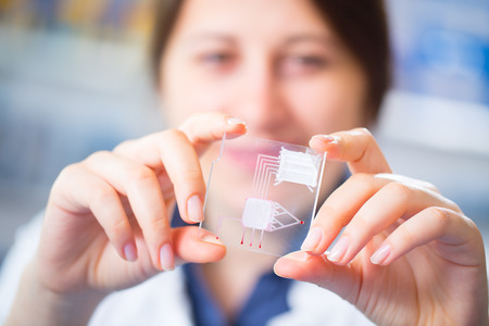integrates: A lab on chip is device integrates several laboratory processes in one device, in woman hand Stock Photo
