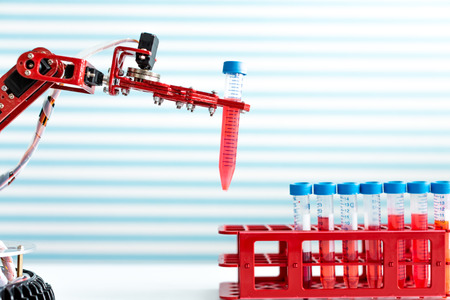 chemical reaction: robot manipulates test tubes with dangerous chemicals Stock Photo