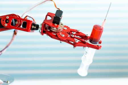 Robot holding a medical syringe Stock Photo