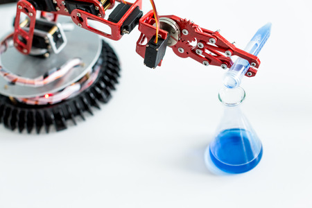 robot manipulates test tubes with dangerous chemicals Standard-Bild
