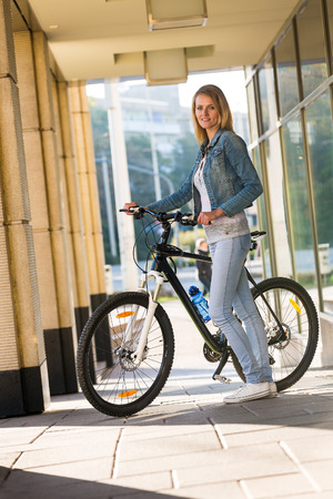 young beautiful woman: young happy smiling blonde beautiful woman wearing in white jeans riding bikes in park in bright sunlight on summer day Stock Photo