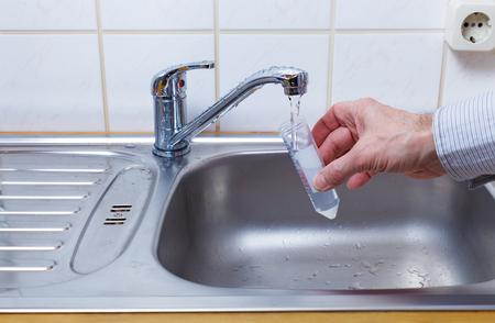 vaso con agua: El agua potable en el tubo de ensayo para el análisis químico y microbiológico