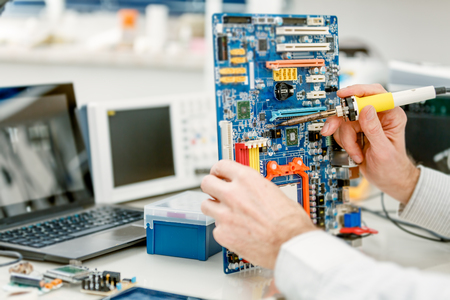 people working: Tech tests electronic equipment in service centre