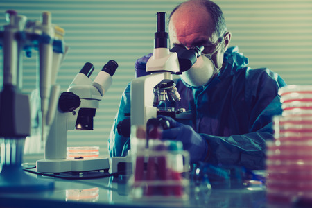scientific equipment: scientist looking at microscope in chemistry laboratory