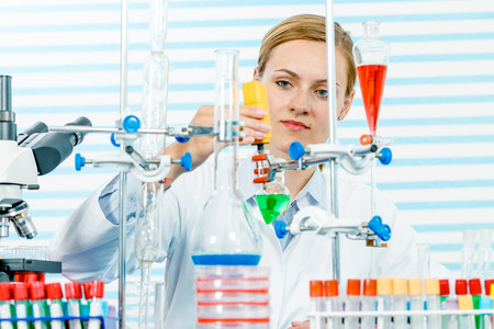 chemical laboratory: Chemical laboratory scene: attractive young  student scientist observing the blue indicator color shift after the solution destillation. Stock Photo