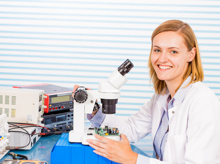 peering: A young female researcher in a lab coat is peering into a microscope