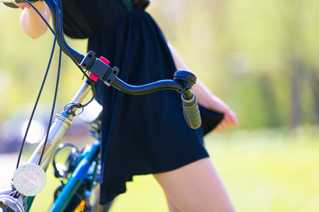 summer dress: Slim girl in short  dress and bike in park Stock Photo