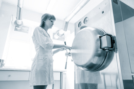 setup operator: pharmaceutical factory woman worker operating autoclave for medicine drug steam sterilization at pharmacy industry manufacture factory