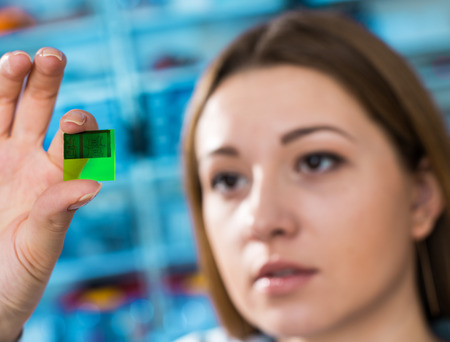 assays: A lab on chip is device integrates several laboratory processes in one device, in woman hand Stock Photo