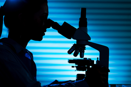 Silhouette of a scientist at microscope
