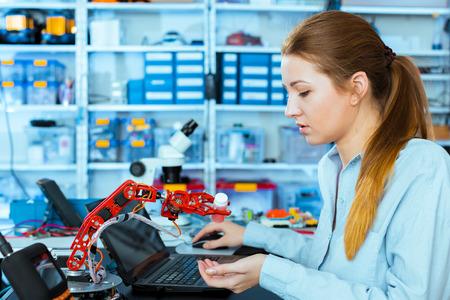 schoolgirl adjusts the robot arm model, girl in a robotics laboratory Archivio Fotografico