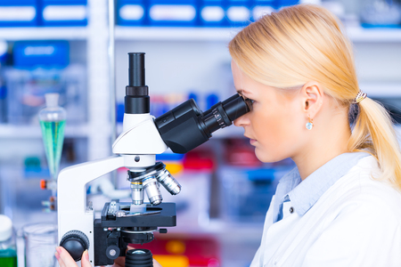 appearance: Scientist using a microscope in a laboratory Stock Photo