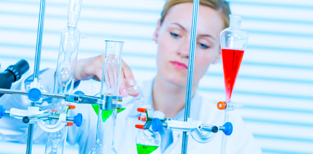 health woman: Chemical laboratory scene: attractive young student scientist observing the blue indicator color shift after the solution destillation.