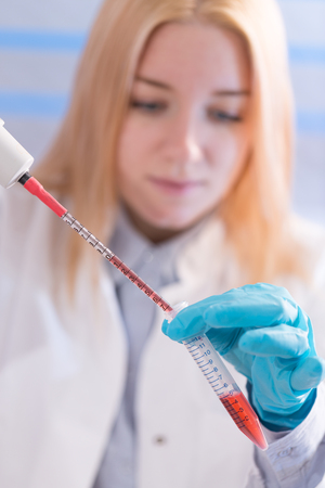 woman assistant in laboratory with multi pipette in the clinic, the research of cancer stem cells