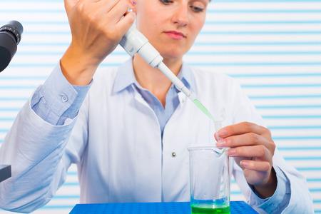 tige: femme assistante dans un laboratoire multi pipette à la clinique, la recherche des cellules souches du cancer Banque d'images