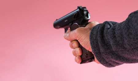 Gun in man hand on pink background