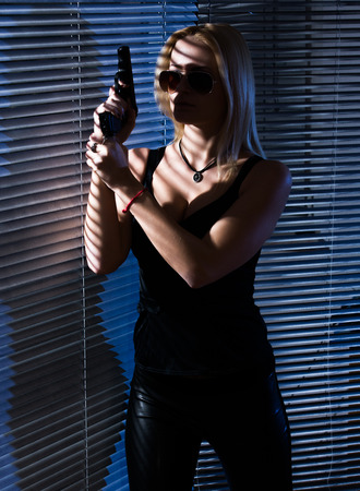 girl secret agent with gun hidden behind jalousie